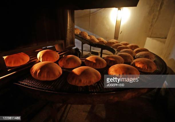 Freshly-baked bread moves along a production line out of an oven at an automated bakery in Lebanon's capital Beirut on July 1, 2020. - The Lebanese...