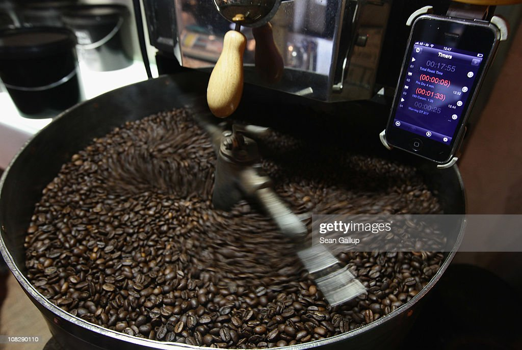 Freshly-roasted espresso coffee beans cool under an iPhone with a timer app attached to a refurbished 1918 Probat coffee bean roaster at Bonanza Coffee Roasters on January 24, 2011 in Berlin, Germany. Bonanza founder Kiduk Reus is among a growing number of so-called third wave artisinal coffee bean roasters who are finding a niche market in Europe and the USA for their carefully-crafted and expensive coffee. Reus insists that the cast iron parts, the slow-roasting abilities and hands-on controls of his flame-roasting Probat machine allow him to develop the most flavour from his carefully selected beans.