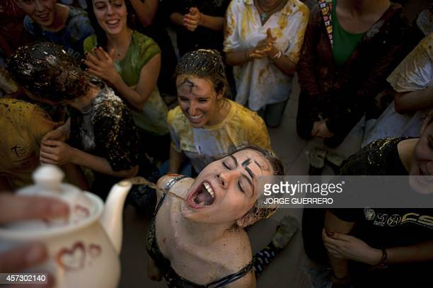 A freshman year medical student has liquid poured into her mouth from a teapot during a faculty of medicine hazing at the University of Granada in...