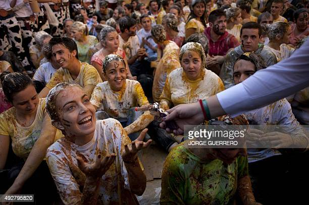 Freshman year medical students covered with food stuffs gesture during the faculty of medicine hazing at the University of Granada in Granada on...