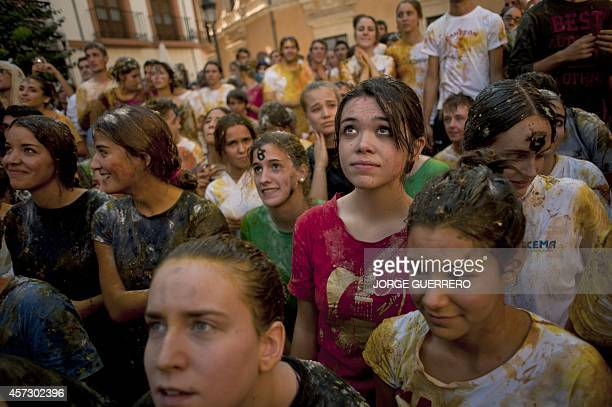 Freshman year medical students covered with food stuffs stand during a faculty of medicine hazing at the University of Granada in Granada on October...
