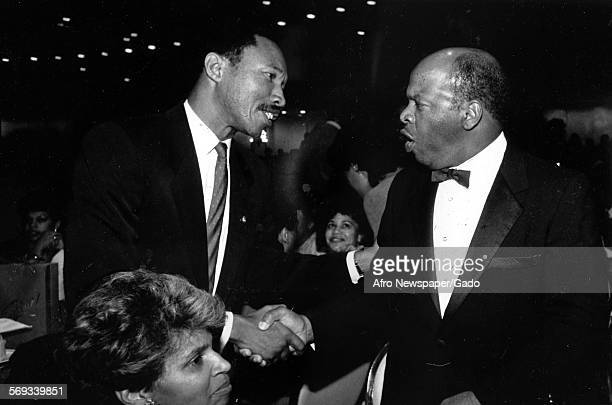 Freshmen Congressmen Kweisi Mfume and John Lewis shaking hands at a formal event Maryland 1987