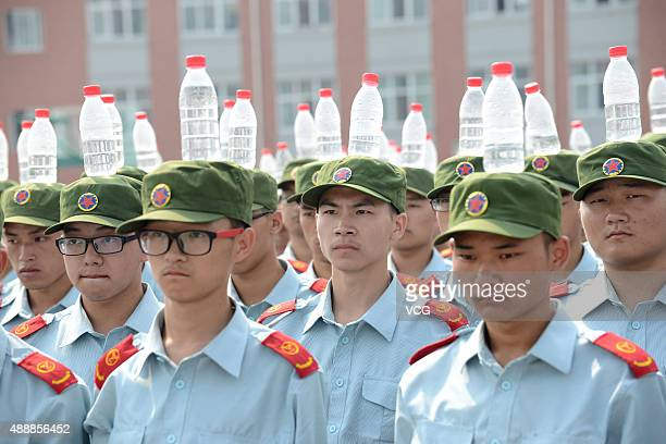 Freshmen in Zhengzhou Institute of Aeronautical Industry Management head bottles of mineral water for upright stand during military training on...