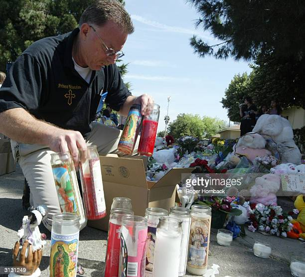 Fresno City Police Chaplain Ed Crain fills a box with candles from the memorial in front of Marcus Wesson's house March 25 2004 in Fresno California...