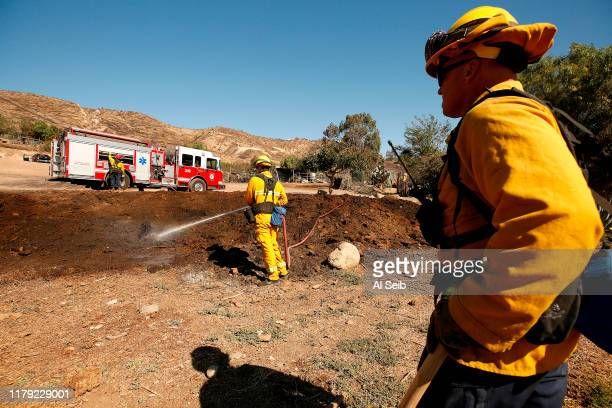 Fresno Fire Firefighters Troy Chaput left and Jamen Elliott right work to extinguish a mulch pile at a ranch along Tierra Rejada road in Simi Valley...