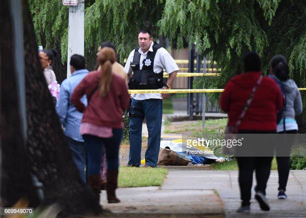 A Fresno police detective stands over the body of one of the three shooting victims as office workers are evacuated on Fulton Street just north of...