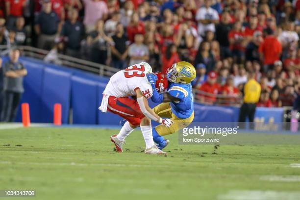 Fresno State Bulldogs running back Josh Hokit is being tackled by UCLA Bruins defensive back Darnay Holmes during a college football game between the...