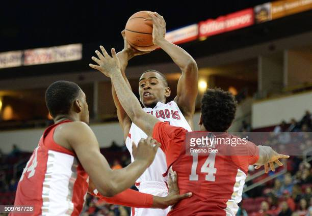 Fresno State's Bryson Williams center looks to pass with UNLV's Brandon McCoy left and Tervell Beck defending in the first half on Tuesday Jan 23...