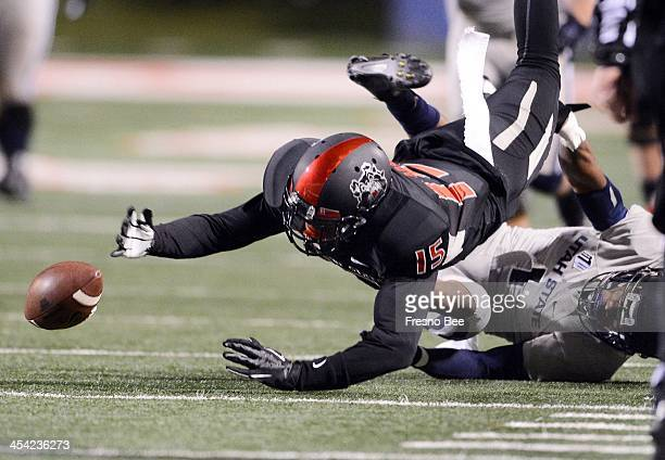 Fresno State's Davante Adams center loses the ball while being tackled by Utah State's Nevin Lawson in the first half of the Mountain West Conference...