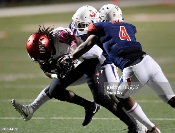 Fresno State's Mike Bell right and Tank Kelly background tackle UNLV wide receiver Devonte Boyd left in the first half on Saturday Oct 28 at Bulldog...