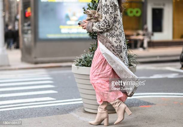 Freya Drohan is seen wearing a black and white floral coat and pink dress with snake skin bag outside the Christian Siriano show during New York...