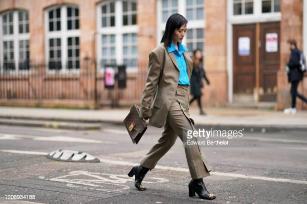 Freya Sinyu Siu wears a white shirt, a beige oversized blazer jacket, a chain belt, flared pants, black leather boots from Balenciaga, a Vuitton bag,...