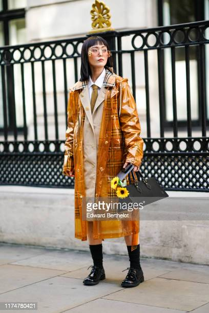Freya Sinyu Siu wears sunglasses a transparent pvc plastic trench coat over a a gray trench coat with checked brown pattern inserts a white shirt a...