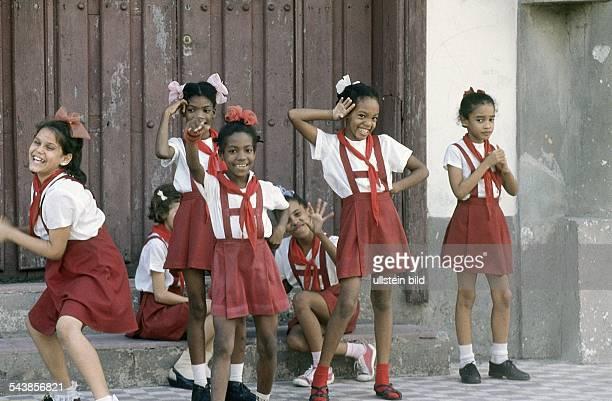 Fröhliche kleine Mädchen in rotweißer Schuluniform winken und kokettieren am Straßenrand in Santiago de Kuba Undatiertes Foto
