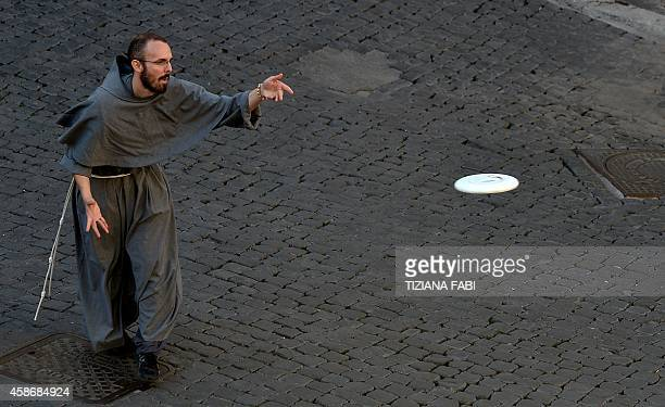 A friar plays frisbee at Piazza Santi Apostoli on November 9 2014 in Rome AFP PHOTO / TIZIANA FABI