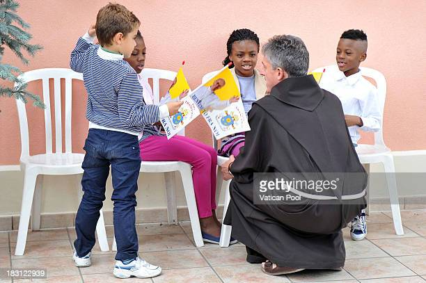 A friar talks with children as Pope Francis visits the Caritas Diocesana on October 4 2013 in Assisi Italy During the Mass Pope Francis called for an...
