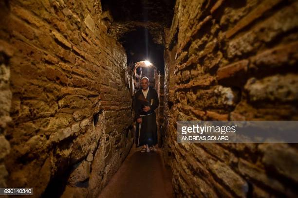 A friar walks towards the restored 'dei Fornai' cubicle during a visit after the restoration of the catacomb of Santa Domitilla in central Rome on...