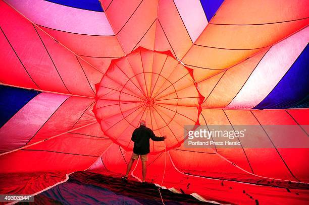 Friday August 16 2013 Pilot Joe Caputo does a last minute check inside the envelope as he and 20 balloons took off from Lewiston's SimardPayne...
