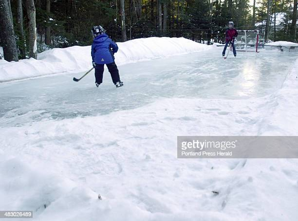 Sam and Ariel Potter play hockey on the backyard rink their father built at their Yarmouth home One corner of the rink turned out to be much higher...