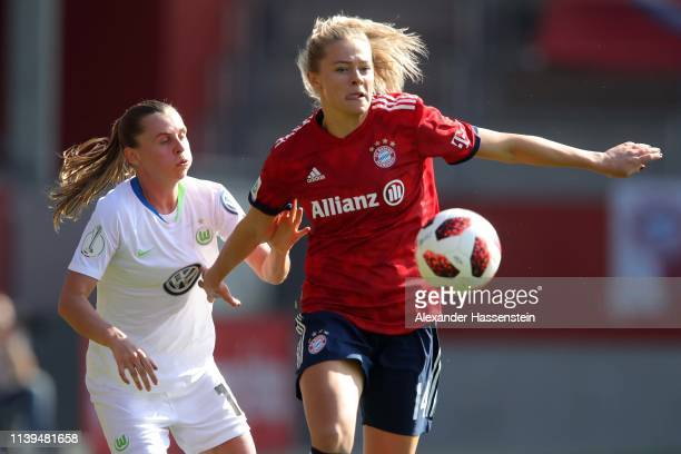 Fridolina Rolfoe of Muenchen battles for the ball with Noelle Maritz of Wolfsburg during the DFB Cup Semi Final match between FC Bayern Muenchen and...