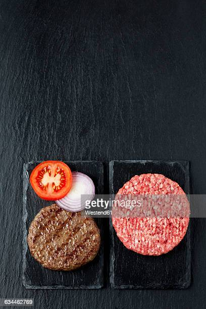 Fried and raw beef patties with tomato and onion rings