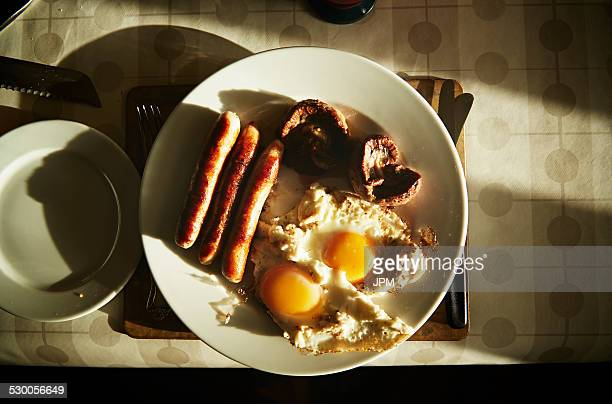 Fried breakfast of sausages, eggs and mushrooms on table