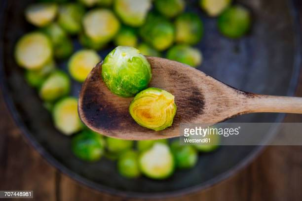 Fried Brussels sprouts on cooking spoon, close-up