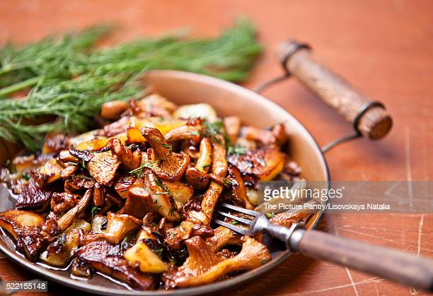 Fried chanterelles with potatoes and onion in batch pan on the t