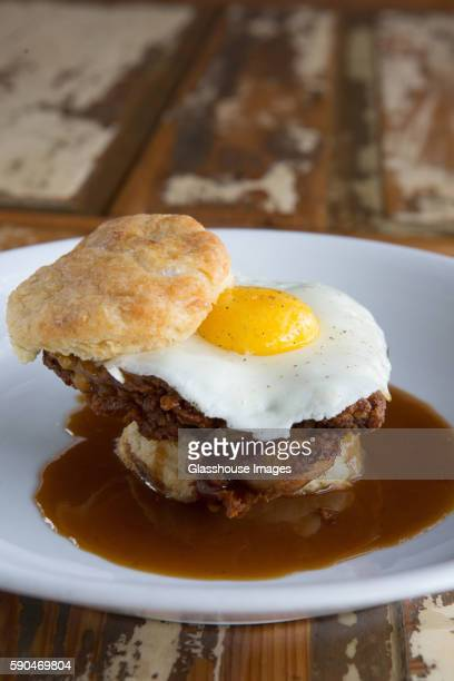 Fried Chicken and Egg on Biscuit in Plate of Gravy