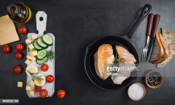 Fried chicken breast on a cast iron frying pan and fresh sliced vegetables