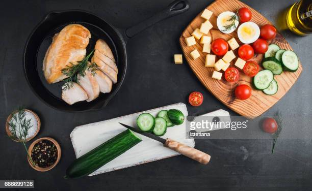 Fried chicken breast on a cast iron frying pan. Preparation salad,  top view