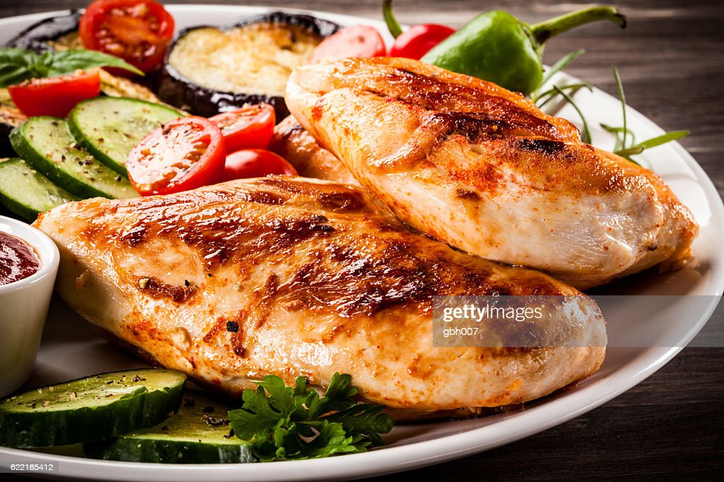 Fried chicken fillets and vegetables on wooden background