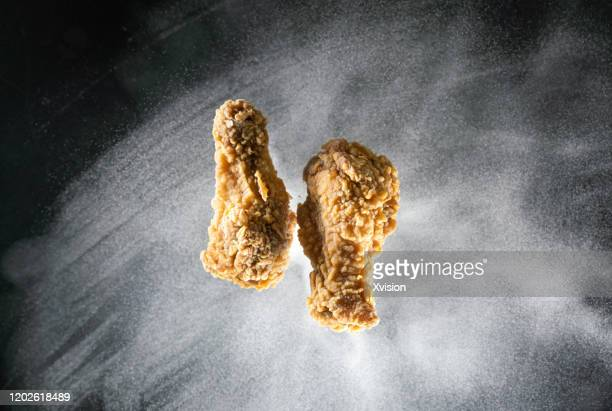 fried chicken meat flying in mid air captured with high speed sync. - chicken wings stock pictures, royalty-free photos & images