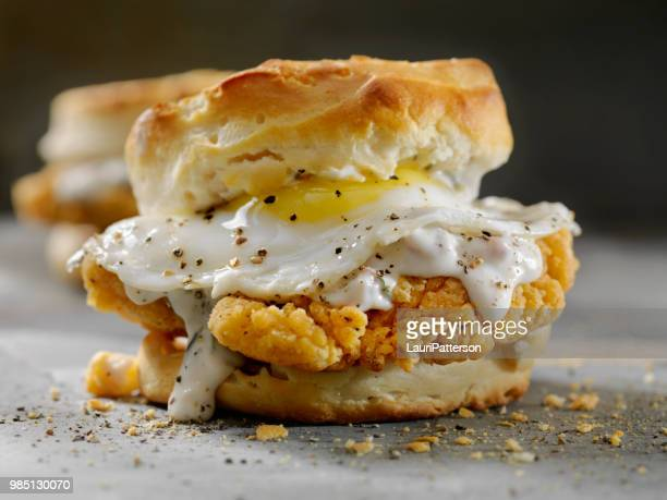fried chicken sandwich with a fried egg,sausage gravy on a biscuit - biscuit stock photos and pictures