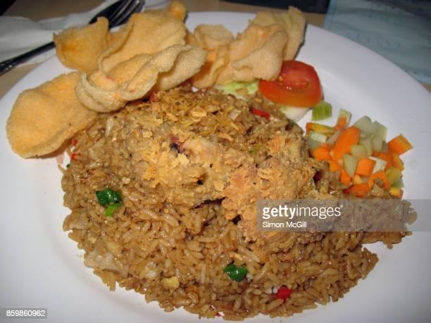 fried chicken served on top of nasi goreng (indonesian fried rice), with prawn crackers and raw tomato, cucumber and carrot - indonesian culture stock pictures, royalty-free photos & images