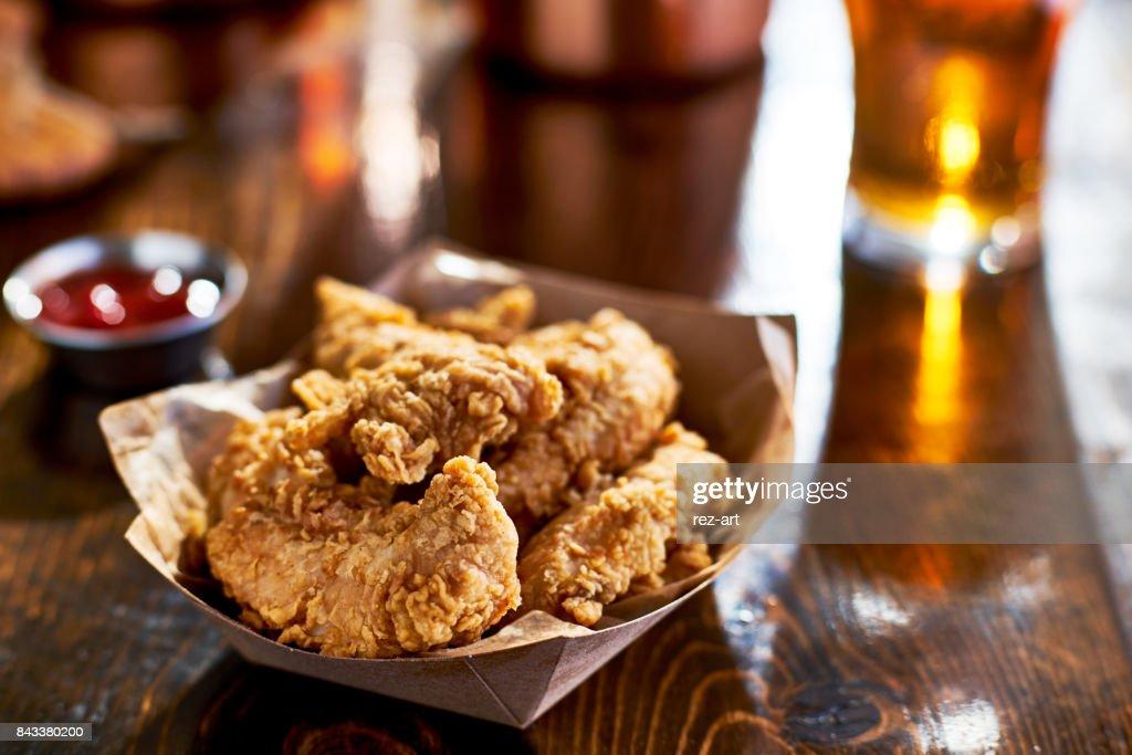 fried chicken tenders in paper basket : Stock Photo