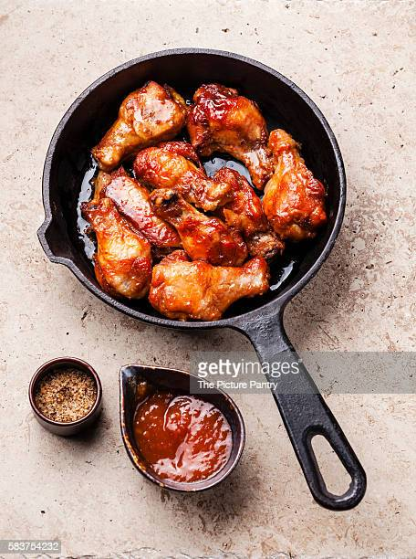 Fried Chicken Wings with sauce on black pan