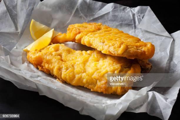 Fried coalfish filet and lemon slices on greaseproof paper