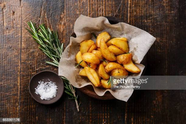 Fried Country-style Potato wedges and salt on wooden background