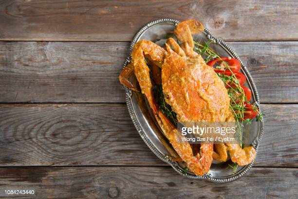 fried crab and vegetables in tray on table - chilli crab stock photos and pictures