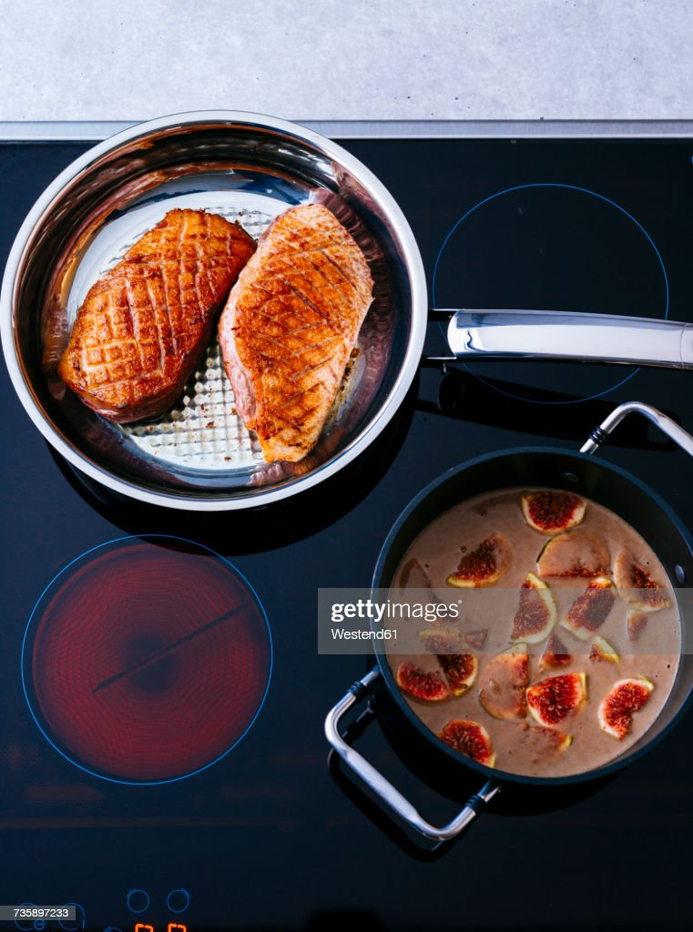 Fried duck breast and pot of fig sauce on cook top : Stock Photo