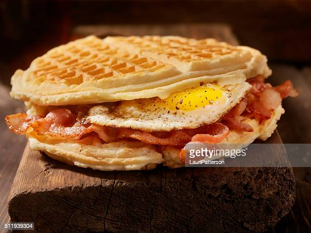 fried egg and bacon waffle sandwich - chicken and waffles stock photos and pictures