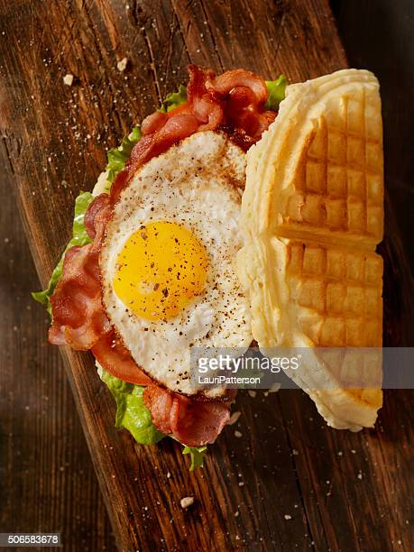 fried egg, bacon, lettuce and tomato waffle sandwich - chicken and waffles stock photos and pictures