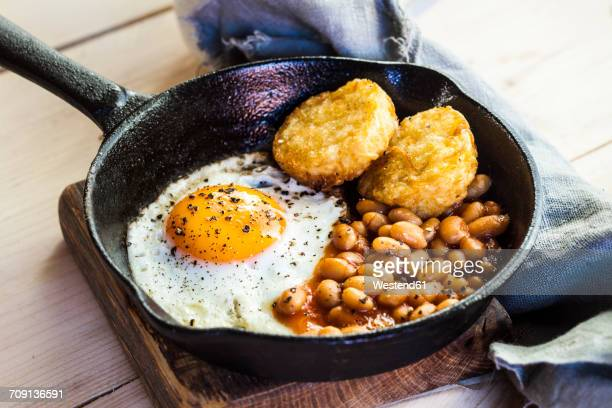 Fried egg, baked beans and hash browns in frying pan on wooden board