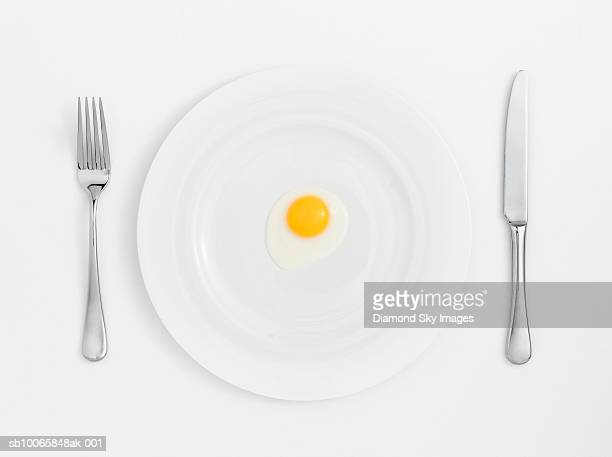 fried egg on plate with knife and fork, close-up - forchetta foto e immagini stock