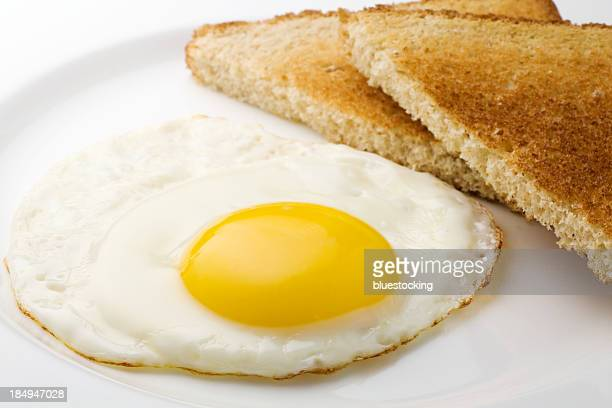 fried egg sunny side up and plain sliced toast - fried eggs stock pictures, royalty-free photos & images