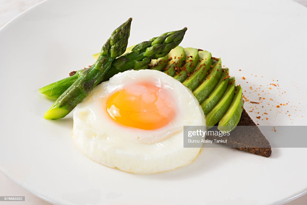 fried egg with avocado and asparagus : Stock Photo