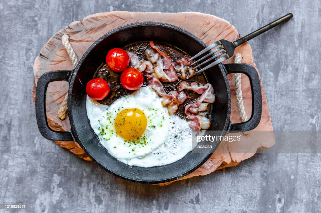 fried egg with bacon and tomatoes : Stock Photo