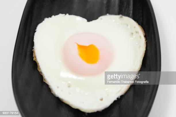 fried egg with heart shape - egg white stock pictures, royalty-free photos & images