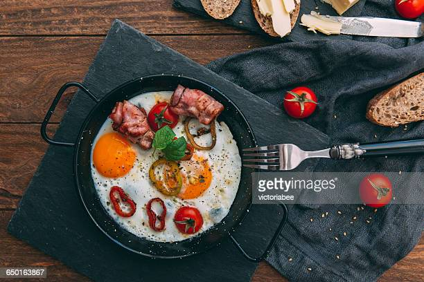 Fried eggs, bacon and cherry tomatoes with bread